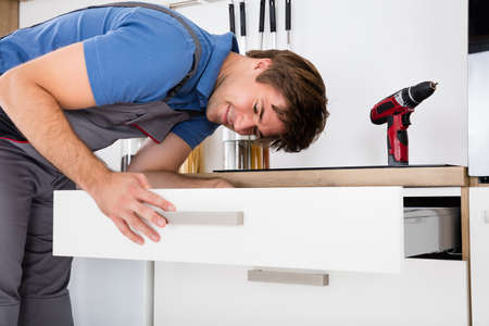 installing: Happy Young Carpenter Fixing Drawer In Kitchen