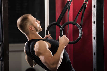 Fitness Man Pulling Up On Gymnastic Rings In The Gym