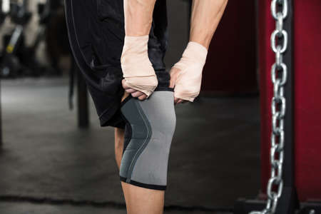 flexion: Close-up Of A Person Preparing For Training Wearing Knee Bandage In The Gym Stock Photo