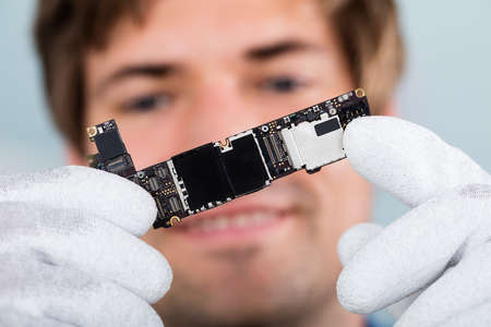 Close-up Of A Happy Man Holding Smart Phone Circuit Board Wearing Glove Stock Photo