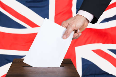 Businessperson Hand Putting Vote Into Ballot Box In Front Of United Kingdom Flag Stock Photo