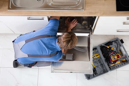 High Angle View Of Man In Overall Repairing Dishwasher In Kitchen