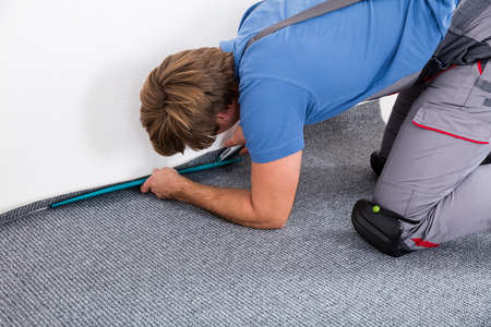Rear View Of A Craftsman Fitting Carpet On Floor Standard-Bild