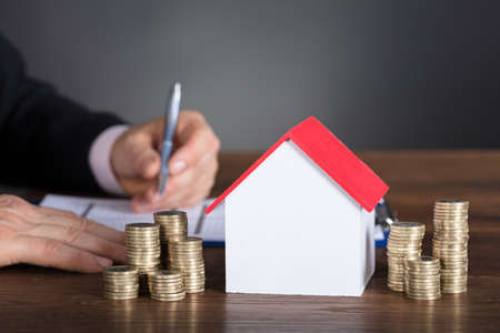 Hombre de negocios cálculo de impuestos de modelo de casa y pilas de monedas en la tabla