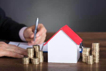 Homme d'affaires, calcul de l'impôt par la maison modèle et piles de pièces sur la table