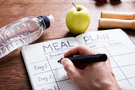 High Angle View Of A Person Hand Filling Meal Plan In Notebook At Wooden Desk Stock Photo