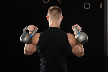 fit: Rear View Of A Young Athlete Man Doing Exercise With Kettle Bell In The Gym Stock Photo