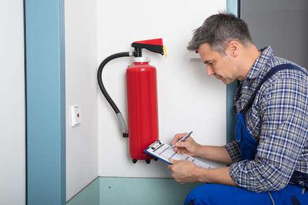 Nahaufnahme eines männlichen Berufs Überprüfung einen Feuerlöscher Zwischenablage Standard-Bild - 73201536