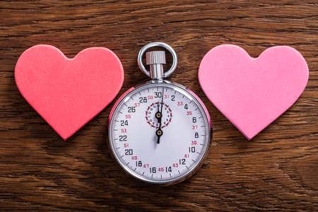 스피드 데이트 개념. 두 심장 모양과 나무 책상에 그만 시계