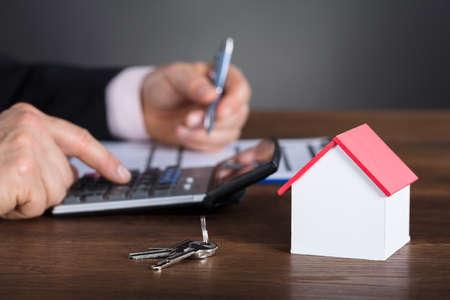 ビジネスマンの計算住宅コストの家モデルや木製の机の上のキーに計算機を使用して