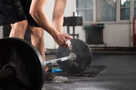 talc: Weightlifter Hand Applying Talc Powder Before Doing Exercise With Barbell In Gym  Stock Photo