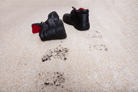 High Angle View Of A Pair Of Shoes With Mud Lying On Carpet Floor