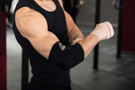elbow band: Close-up Of An Athlete Person Wearing Bandage On Elbow In The Gym