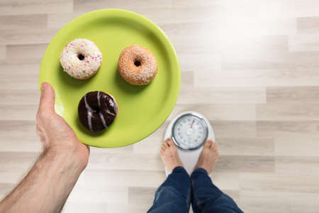 High Angle View Of A Person Holding Plates Of Donut Standing On Weighing Machine Stock Photo
