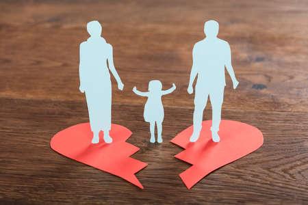 Primer plano de un papel familiar cortado en un corazón roto en el escritorio de madera Foto de archivo - 73495332