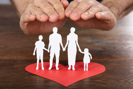 heart in hand: Person Hand Protecting Family Paper Cut With Red Heart On Wooden Desk