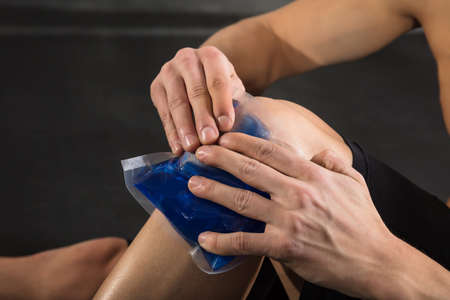 packs: Close-up Of A Person Applying Ice bag On An Injured Knee In The Gym Stock Photo