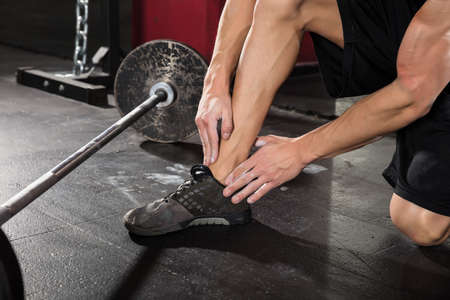 cramp: Close-up Of A Man Suffering From Ankle Pain After Exercise In The Gym