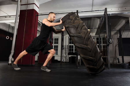 huge: Young Athlete Man Pushing Truck Tire In The Gym