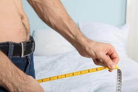 pene: Primer plano de un hombre usando cinta métrica en Jean en casa Foto de archivo