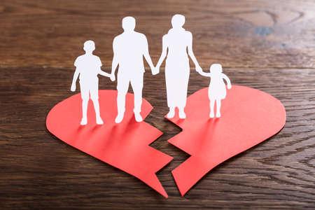 Primer plano de un corte familiar de papel en el corazón roto en el escritorio de madera