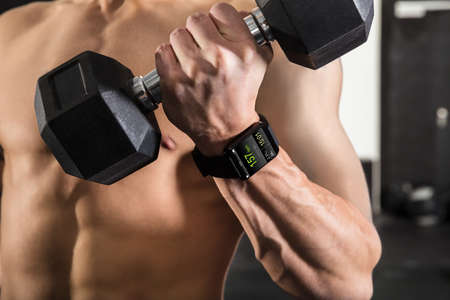man gym: Close-up Of A Athlete Man Wearing Smart Watch While Exercising With Dumbbell In The Gym