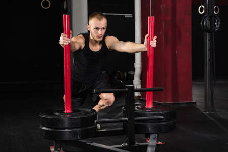 prowler: Young Athlete Man Getting Trained On Gym Equipment In Gym