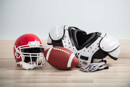 Rugby Ball With Gloves And Helmet On Hardwood Floor Stock Photo