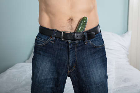 horny: Close-up Of A Person With A Cucumber Stuffed Down His Pants At Home
