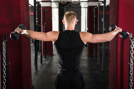Rear View Of Young Man Getting Trained With Dumbbell In Gym
