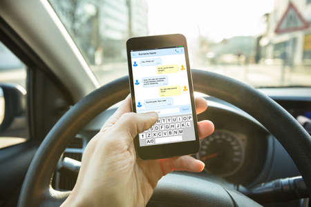 Close-up Of A Person Sending A Text Message Using Mobile Phone While Driving A Car Stockfoto