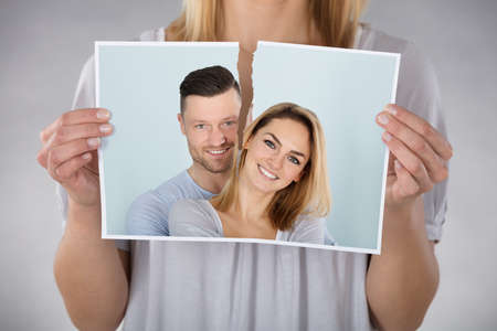 tearing: Close-up Of Woman Tearing Photo Of Smiling Couple