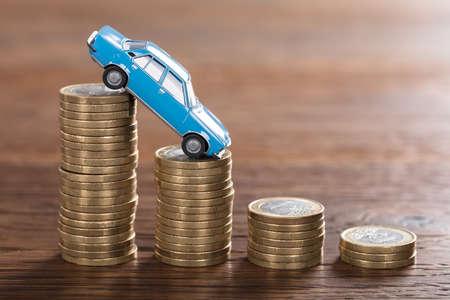Close-up Samochodu Model Nad Stacked Coin W Drewnianych Biurko Zdjęcie Seryjne