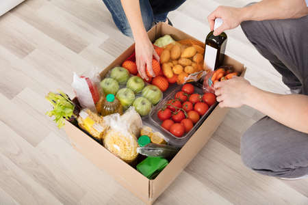 Close-up Of Couple With Groceries In Cardboard Box