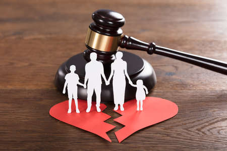 Close-up Of A Family Paper Cut On Broken Heart With A Gavel At Wooden Desk Stok Fotoğraf