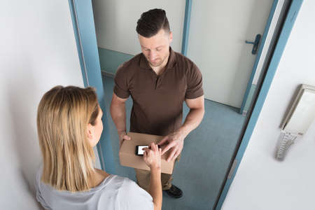 receiving: View Of A Young Woman Signing After Receiving Box From Delivery Man Stock Photo