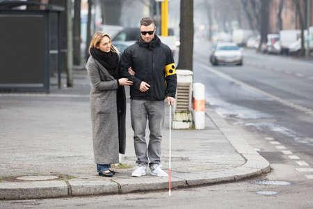 Jonge Vrouw Assisteren Blind Man Met Witte Stok Op Straat Stockfoto
