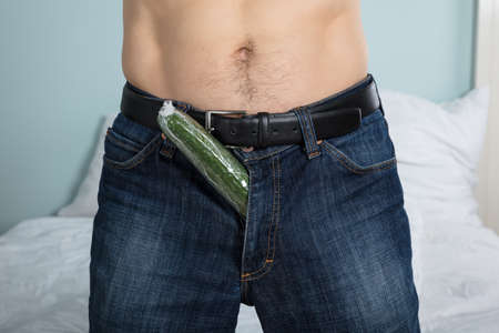Close-up Of A Person With A Cucumber Stuffed Down His Pants At Home