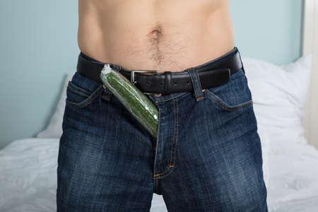 pene: Primer plano de una persona con un pepino rellenos bajó los pantalones en casa