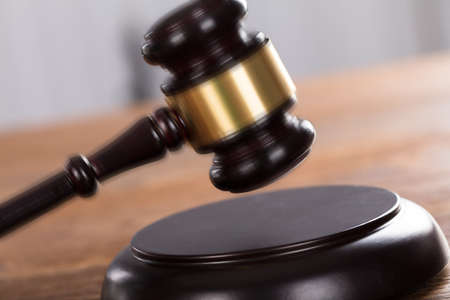 Close-up Of A Gavel Striking On Wooden Desk In A Courtroom Stock Photo