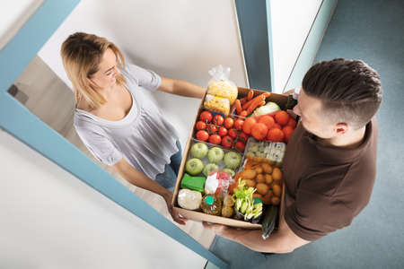 Elevated View Of Smiling Young Woman Accepting Cardboard Box Full Of Groceries From Delivery Man