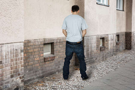 disrespect: Rear View Of A Man Peeing On The Wall Of A Building