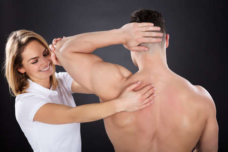 Young Smiling Female Physiotherapist Giving A Man Shoulder Massage Against Grey Background