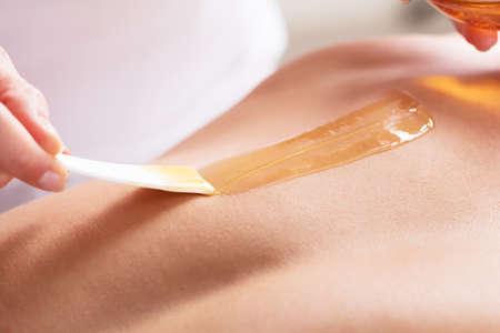 depilacion con cera: Primer plano de una mujer encerar el pecho del hombre con la tira de cera