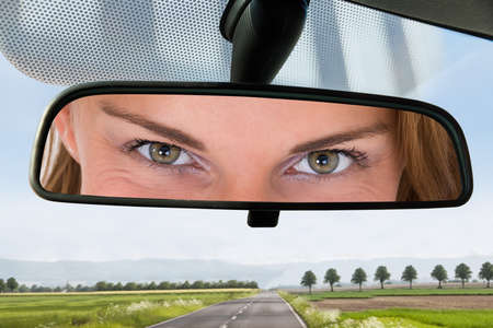 Close-up Of A Woman Eye On The Rear View Mirror Of A Car