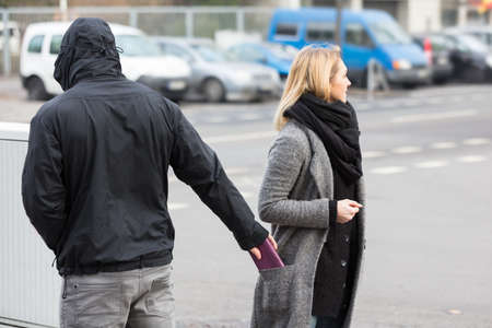 Man In A Hood Stealing Purse From Womans Coat Pocket On Street Stok Fotoğraf