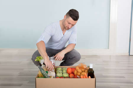 delivery room: Young Man Checking The Groceries In The Box At Home