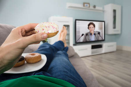 Close-up Of A Person Eating Donut While Watching Television At Home photo