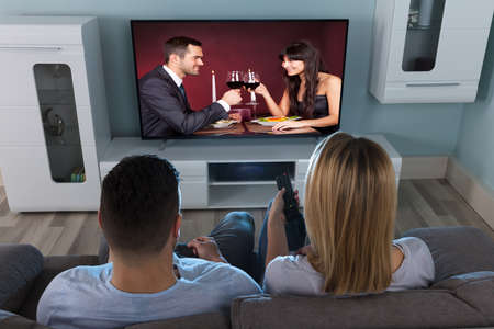 Close-up Of A Couple Watching Couple Enjoying Drink On Television At Home photo