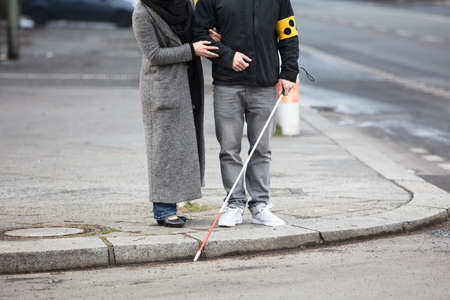 Close-up Of A Woman Standing With A Blind Man On Street